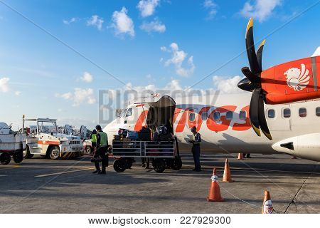 Bali, Indonesia - July 23, 2017: Airport Worker Loads Baggages Into Thai Lion Air Boeing 737 Airplai