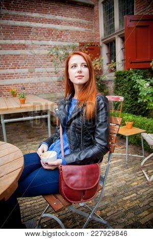 Young Redhead Girl In Hat In A Cafe In Amsterdam