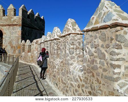 Tourist Wandering On The Medieval City Walls Of Avila, Spain