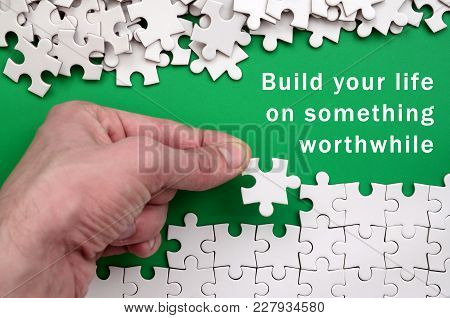 Build Your Life On Something Worthwhile. The Hand Folds A White Jigsaw Puzzle And A Pile Of Uncombed