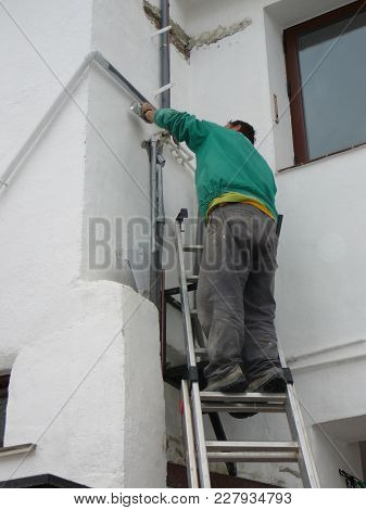 Alora, Spain - December 14, 2011: Man Spray Painting Newly Installed Pvc Pipes