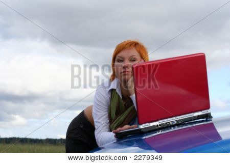 Young Woman With Red Notebook On Cowl Of Blue Car