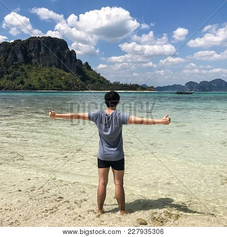 Back View Of Young Man Spread His Hands On Beach. Man On Beach Hold Hands Arms Up, Rear View Guy, St