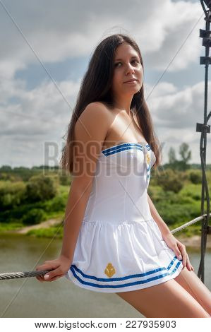 Pretty Woman In White Sailor Costume Standing On Old Wooden Cable Bridge
