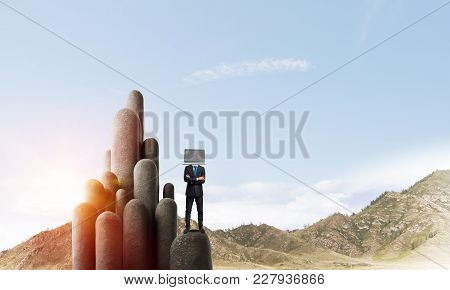 Businessman In Suit With Laptop Instead Of Head Keeping Arms Crossed While Standing On The Top Of St