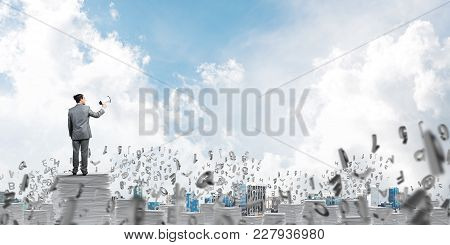 Businessman In Suit Standing Among Flying Letters With Speaker In Hand And With Skyscape On Backgrou