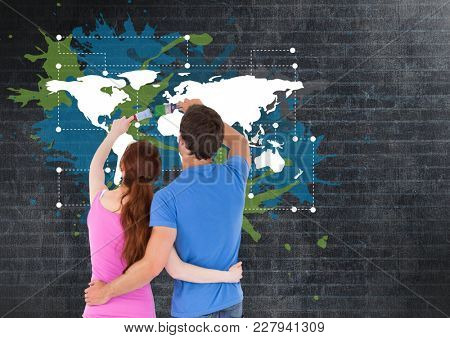 Digital composite of Couple painting a Colorful Map with paint splatters on wall background