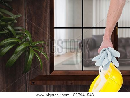 Digital composite of Hand with yellow hat in front of a window of a wood house