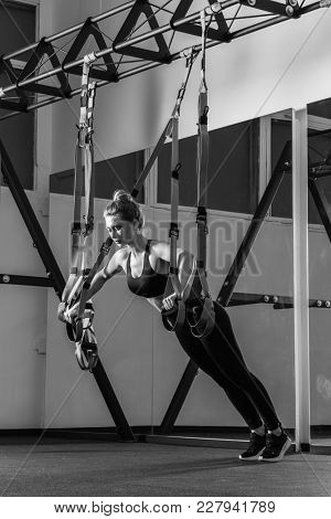 Sporty woman doing TRX exercises in the gym