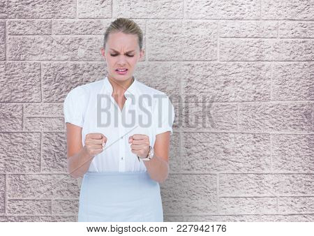 Digital composite of Business woman in front of a wall with look of disgust