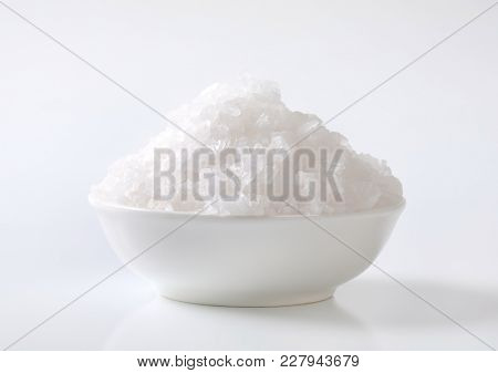bowl of coarse grained sea salt on white background