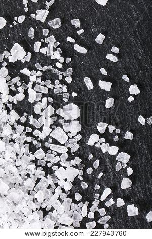 crystals of coarse grained sea salt on black background