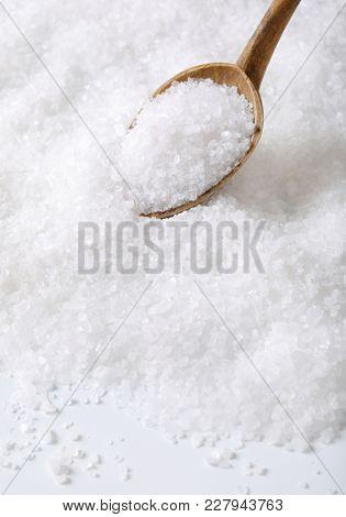 coarse grained sea salt on a wooden spoon