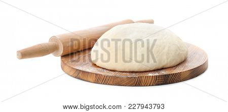 Wooden board with raw dough and rolling pin on white background