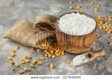 Bowl with corn starch and kernels on table poster