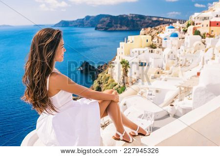 Europe summer travel destination Santorini tourist woman on vacation relaxing. Asian girl in white dress looking at famous white village Oia with the mediterranean sea and blue domes.