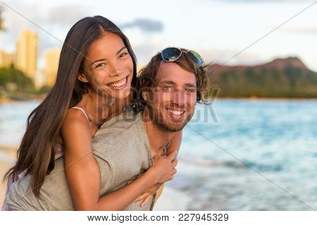 Couple in love on Hawaii travel vacation. Happy Asian woman piggybacking on Caucasian man, multicultural people. Healthy young adults portrait on Waikiki beach, Honolulu, Hawaii.