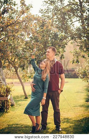 Full-height Portrait Of A Happy Couple In An Autumn Garden