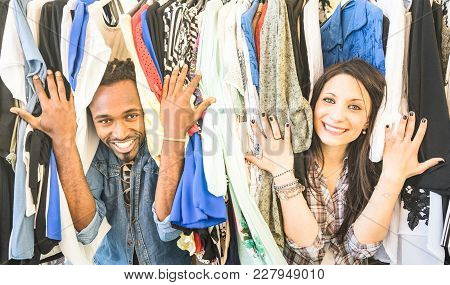 Young Multiracial Couple Having Fun At Clothing Flea Market - Best Friends Sharing Time Shopping On