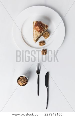 Cake With Bowl Of Walnuts Placed On White Surface