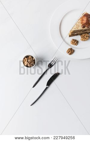 Top View Of Cake On Plate, Walnuts And Cutlery