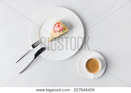 Cheesecake With Strawberry On Top And Cup Of Coffee On Table