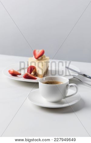 Cheesecake With Strawberries On Plate And Cup Of Coffee On Foreground