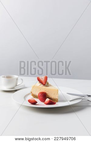 Cheesecake With Strawberries On Plate And Cup Of Coffee On White Table