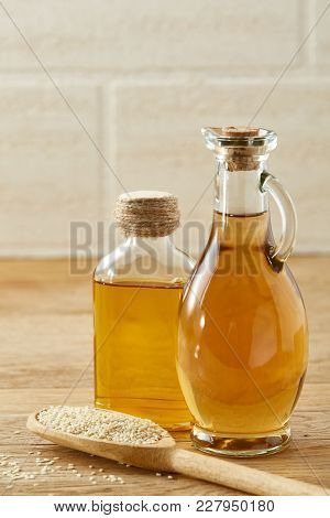Plain Kitchen Still Life Of Transparent Glass Oil Jars And Flat Scoop With Sesam Seeds On Wooden Tab