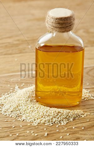 Peeled Sesame Seeds With Oil In A Small Transparent Glass Bottle Over Rustic Wooden Background, Shal