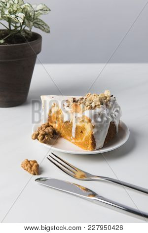 Cake On Plate Near Potplant With Fork And Knife