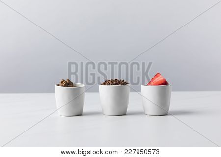 Front View Of Three Bowls With Walnuts, Grated Chocolate And Strawberries