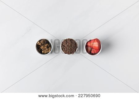 Three Bowls With Walnuts, Grated Chocolate And Strawberries On White