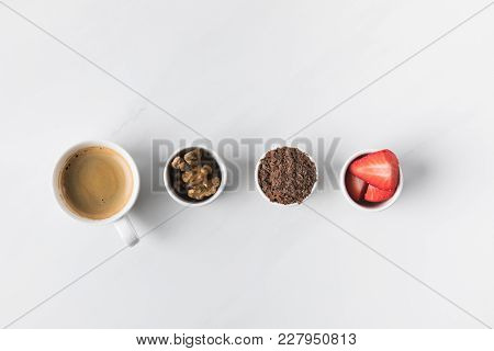Top View Of Coffee Cup And Bowls With Walnuts, Strawberries And Grated Chocolate