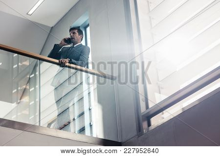 Caucasian Woman Standing In The Office Corridor With A Digital Tablet. Female Executive Looking Away