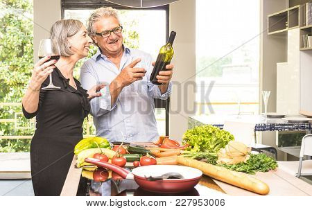 Senior Couple Cooking Healthy Food And Drinking Red Wine At House Kitchen - Retired People At Home P