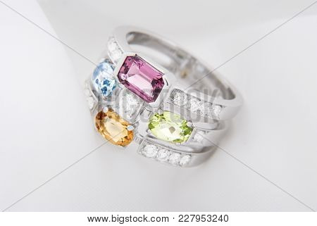 White Gold Ring With Citrine Peridot, Blue Topaz, Pink Tourmaline And Diamonds On Soft White Backgro