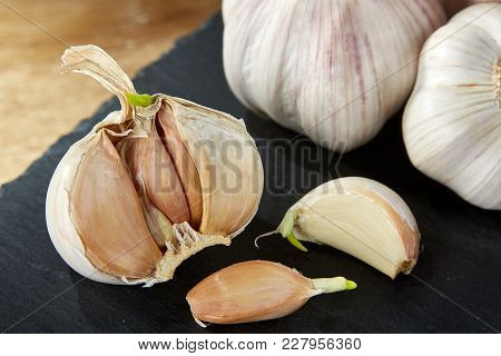 Garlic On Flat Black Piece Of Board. Close-up, Shallow Depth Of Field, Selective Focus, Front Focus,