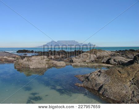 A Clear Summer Day, With Boulders And Calm Blue Water In The Fore Ground And Table Mountain In The B