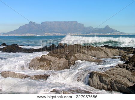 Waves Washing Over Some Rocks In The Fore Ground, With Table Mountain In The Back Ground 20