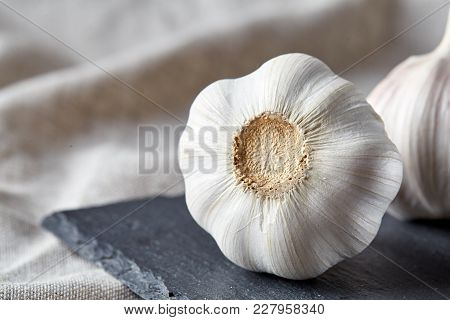Close Up View Of Two Ripe Garlic Bulbs Arranged On A Light Grey Cotton Napkin Or Tablecloth, Shallow