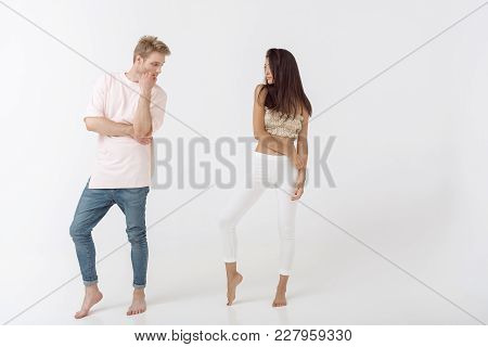 Fashionable Man And Woman Posing Indoors Standing In Studio Against White Background. Interracial Co