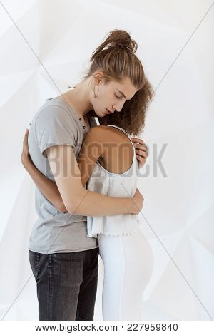 Young Mixed-race Couple In Love Hug Each Other Indoors. Shot Of A Passionate Young People In Love Is