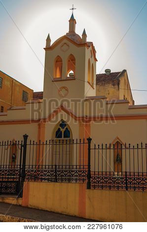 Facade Of Small Church And Belfry, Behind Iron Fence, With Sunshine Behind At Sunset In São Manuel.