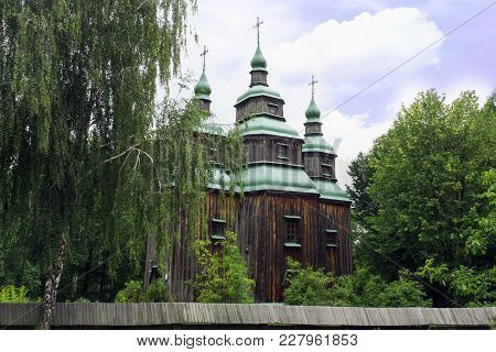 Very Old Wooden Church On The Outskirts Of The Clearing In Front Of The Deciduous Forest On A Clear