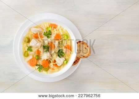 An Overhead Photo Of A Plate Of Chicken, Vegetables, And Noodles Soup, Shot From Above On A Light Wo