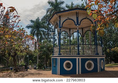 Old And Colorful Gazebo In A Small Square Amid Verdant Garden Full Of Trees, In A Sunny Day At Sao M