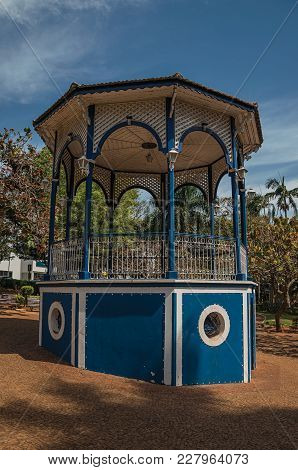 Close-up Of Old Colorful Gazebo In The Middle Of Verdant Garden Full Of Trees, In A Sunny Day At Sao