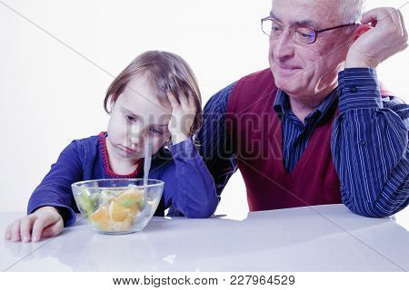 Grandpa Feeding His Grandchild With Fruits Salad. (healthy Foods, Vitamins, Love, Generation, Relati