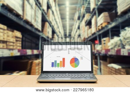 Laptop With Analysis Sale Screen On Table With Blur Warehouse Cargo In Factory. Smart Factory Concep